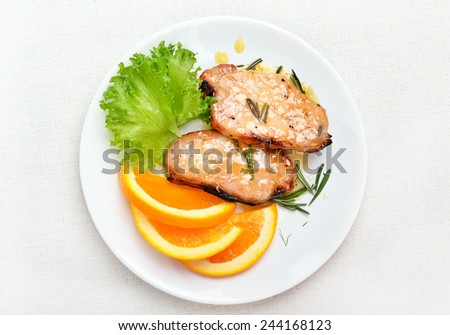 Pork chop with orange sauce on white plate, top view - stock photo