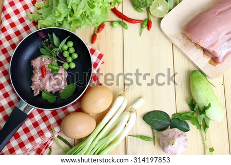 Pork chops and garnish in a pan for preparation of food. Cooking ingredients on a wooden table.  - stock photo