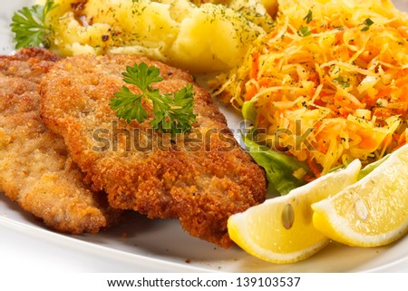 Pork chops, mashed potatoes and vegetable salad - stock photo