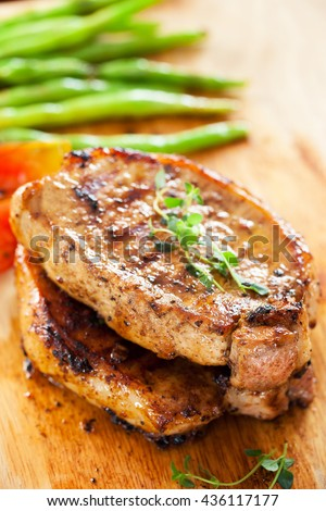 pork chops with thyme and vegetable on wooden board - stock photo