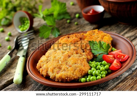 Pork cutlet in bread crumbs with tomatoes and green peas on a wooden table - stock photo