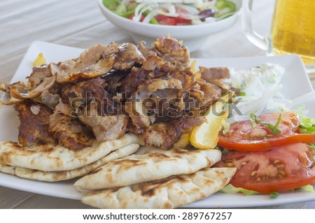 Pork gyros portion served on a plate with vegetables and salad - stock photo