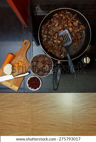 Pork liver stewed with onions and carrot and red beans in  frying pan view 3 - stock photo