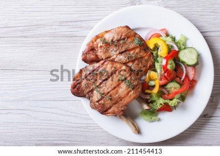 Pork meat grilled with fresh vegetable salad on a white plate. a top view of a horizontal  - stock photo