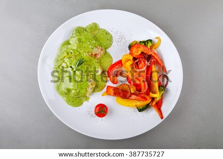 Pork medallions with pesto sauce served on a plate with grelled vegetables. Top view - stock photo