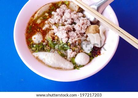 Pork noodle thai food on blue table background. - stock photo