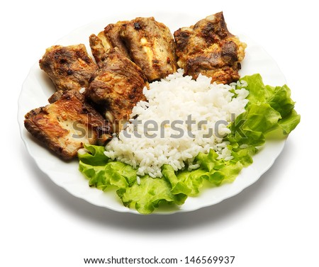 Pork ribs and rice decorated with salad over white background - stock photo