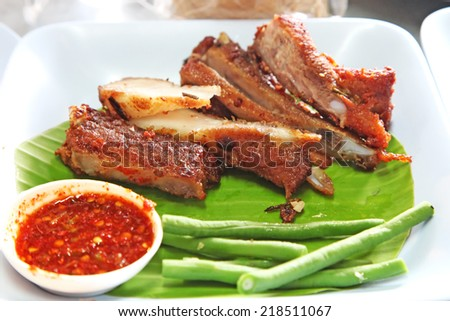 Pork ribs served with chilli sauce and peas - stock photo