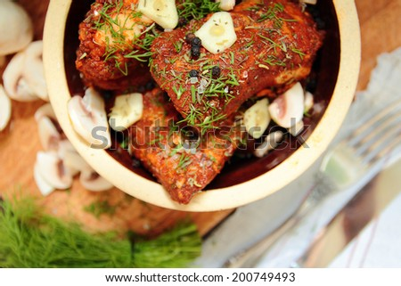 Pork ribs with mushrooms, garlic and fresh herbs - stock photo