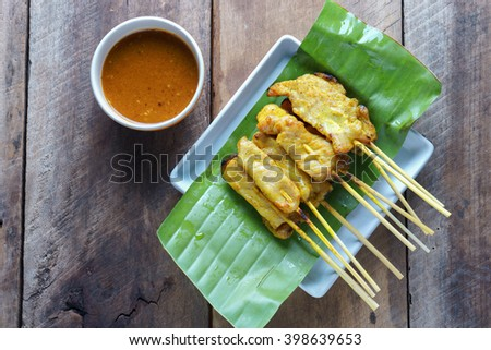 Pork satay,Grilled pork served with peanut sauce or sweet and sour sauce on banana leaf with woodbackground - stock photo