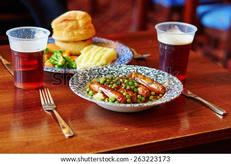 Pork sausages, mashed potatoes, green peas and onion gravy with ale in a traditional English pub - stock photo