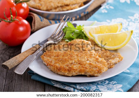 Pork schnitzel with lemon wedges in pan - stock photo