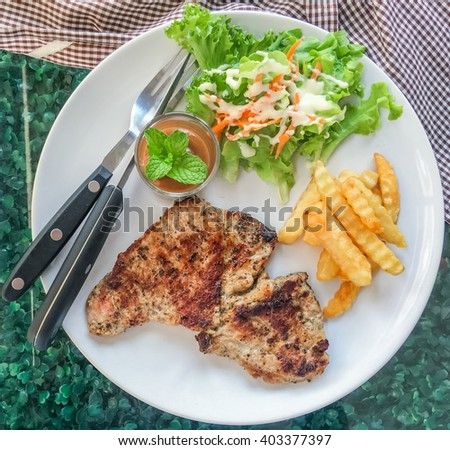Pork steak, french fries and salad on white plate. Top view. - stock photo