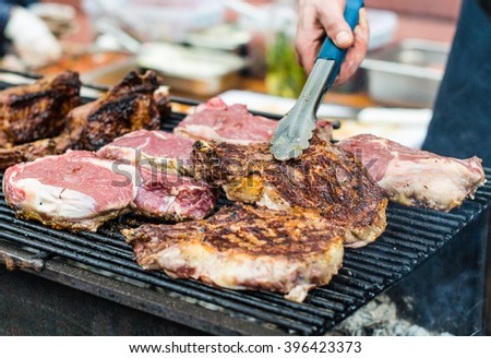 Pork steak fried on the grill grate . The cook prepares a meal at an outdoor market . Close-up on the coals. - stock photo