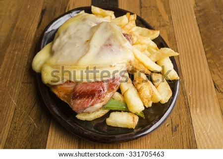Pork steak with melted cheese and fries - stock photo