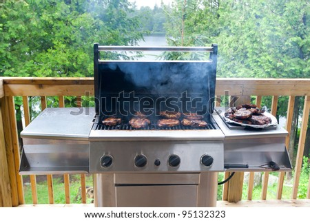 Pork steaks on gas grill in cottage - stock photo