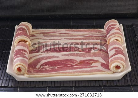 Pork Streaky fresh Bacon on plate with black background - stock photo