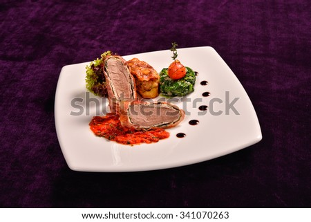 pork tenderloin in bacon wrap with tomato sauce flavored with rosemary and potatoes stuffed with pancetta and cheese, saut�©ed baby spenech - stock photo