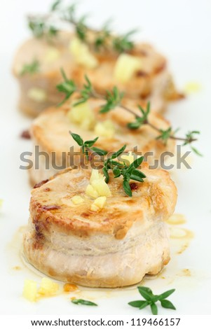 Pork tenderloin medallions with diced ginger and thyme - stock photo