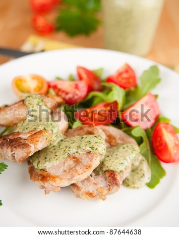 Pork Tenderloin with Cilantro Pesto Served Over Arugula and Tomato Salad - stock photo