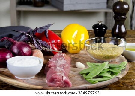 Pork tenderloin with fresh healthy  vegetables, oil and spices.  Raw products on the wooden background - Stock image - stock photo