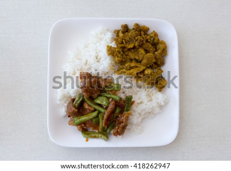 pork with yellow curry paste and stir-fried curry yard long bean with rice on dish  - stock photo