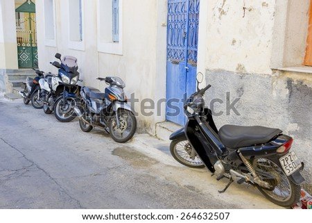 Poros, Greece - September 27, 2014: Several modern scooters parked on old street in Poros island, Greece. - stock photo