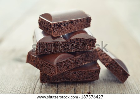 Porous chocolate in stack on a wooden background closeup - stock photo