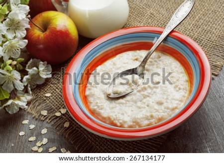 Porridge and red apples on a wooden table - stock photo