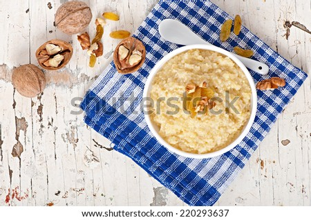 Porridge in a bowl with nuts and raisins - stock photo