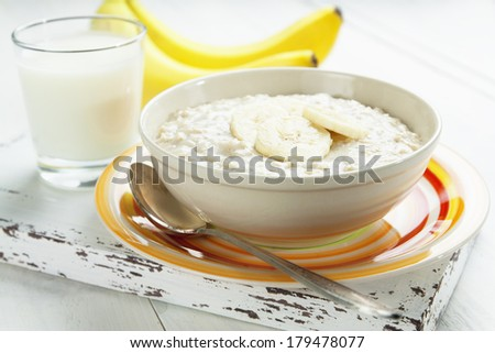 Porridge with bananas in a yellow bowl and a glass of milk on the table - stock photo