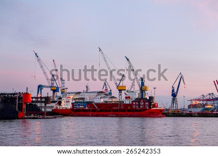 Port and cranes silhouettes at sunset in Hamburg. Germany - stock photo