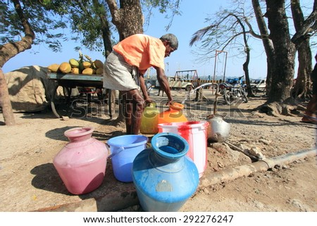 PORT BLAIR, INDIA - FEB 13: An unidentified man collects drinking water from public tap on February 13, 2012 in Port Blair, Andamans,India. Andamans being an Island faces acute drinking water shortage - stock photo