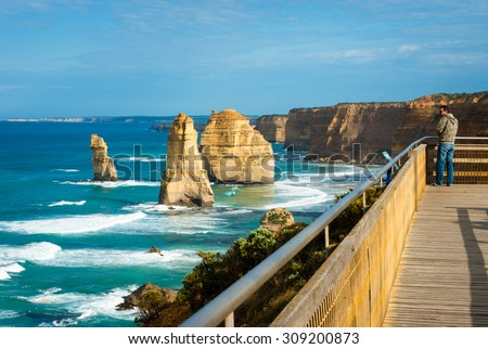 PORT CAMPBELL, AUSTRALIA: OCTOBER 4, 2008: Tourist looks at Twelve Apostles from lookout. The Twelve Apostles along the Great Ocean Rd are one of the most popular tourist destinations in Victoria. - stock photo