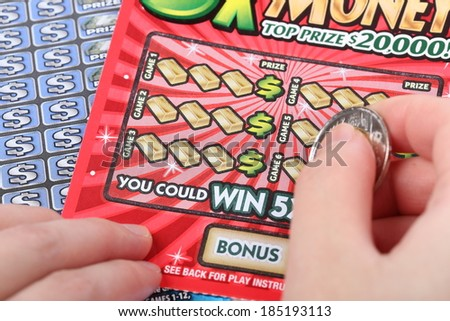 Port Coquitlam BC Canada - March 26 2014 : Scratching a lottery ticket.  The British Columbia Lottery Corporation has provided government sanctioned lottery games in British Columbia since 1985. - stock photo