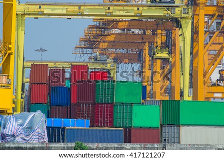 port crane unloads freight cargo ship with containers - stock photo