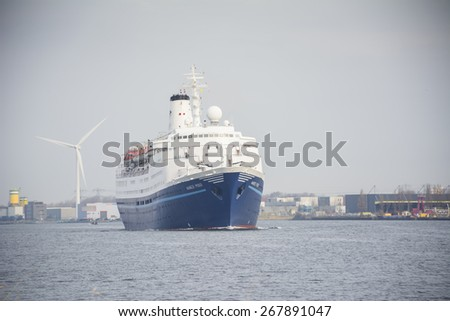 Port of Amsterdam, Noord-Holland/Netherlands - March 28-03-15 - Cruise ship Marco Polo is sailing by sunrise to the Passenger Terminal Amsterdam. Passengers are on board for there vacation. - stock photo
