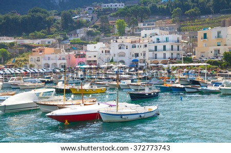 Port of Capri island, Italy. Colorful houses and moored pleasure motorboats - stock photo