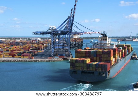 Port of Freeport Bahamas Container shipyard with heavy lifting Cranes and a ship coming in to dock assisted by tug boats - stock photo