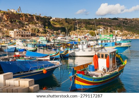 Port of Mgarr on the small island of Gozo, Malta. Traditional maltese colorful painted fishing boat. - stock photo
