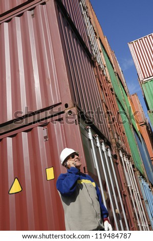 port worker with stacks of shipping containers in background - stock photo
