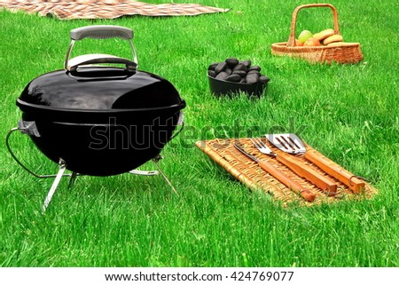 Portable BBQ Grill,  Charcoal Briquettes,Barbecue Tools, Basket With Snack And Fruits, Blanket  On The Fresh Green Lawn, Summertime Picnic Or Cookout Concept - stock photo