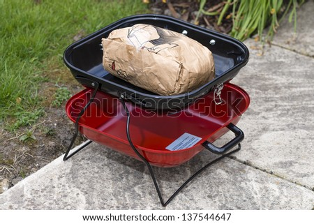 Portable BBQ with unlit instant charcoal. - stock photo