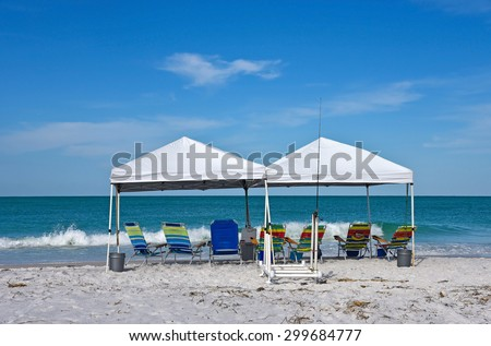 Portable Canopy Shelters with Chairs on the Beach  - stock photo