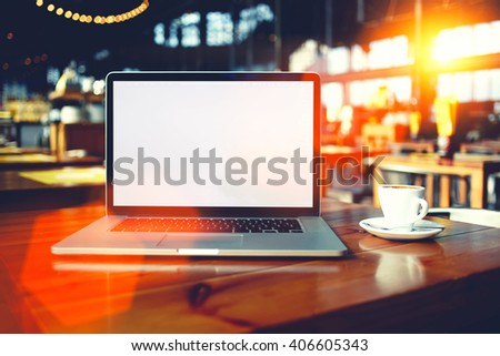 Portable laptop computer with copy space screen for your text message or promotional content, open net-book lying on a table in cafe bar interior, distance work via internet during coffee break - stock photo