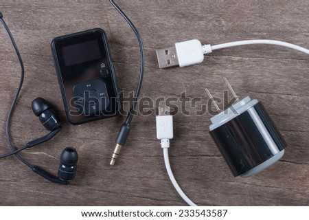 Portable music player with earphone and cable on wooden background - stock photo