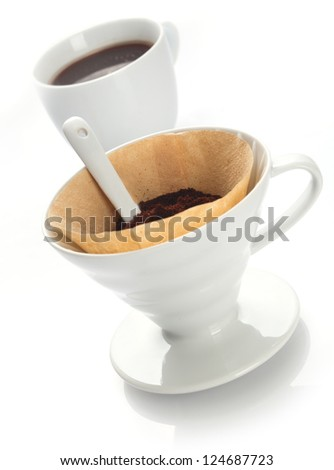 Portable plain white china filter funnel with filter paper filled with freshly ground coffee beans for preparing a fresh brew in a single cup - stock photo