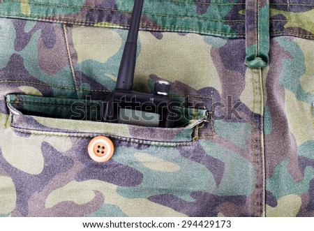 Portable radio in a pocket of pants with camouflage pattern. - stock photo