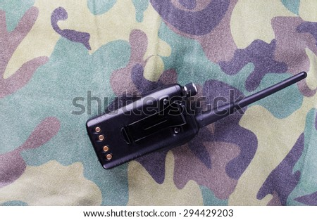 Portable radio on a fabric with camouflage pattern. - stock photo