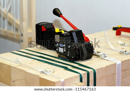 Portable strapping machine for packing crates and boxes - stock photo